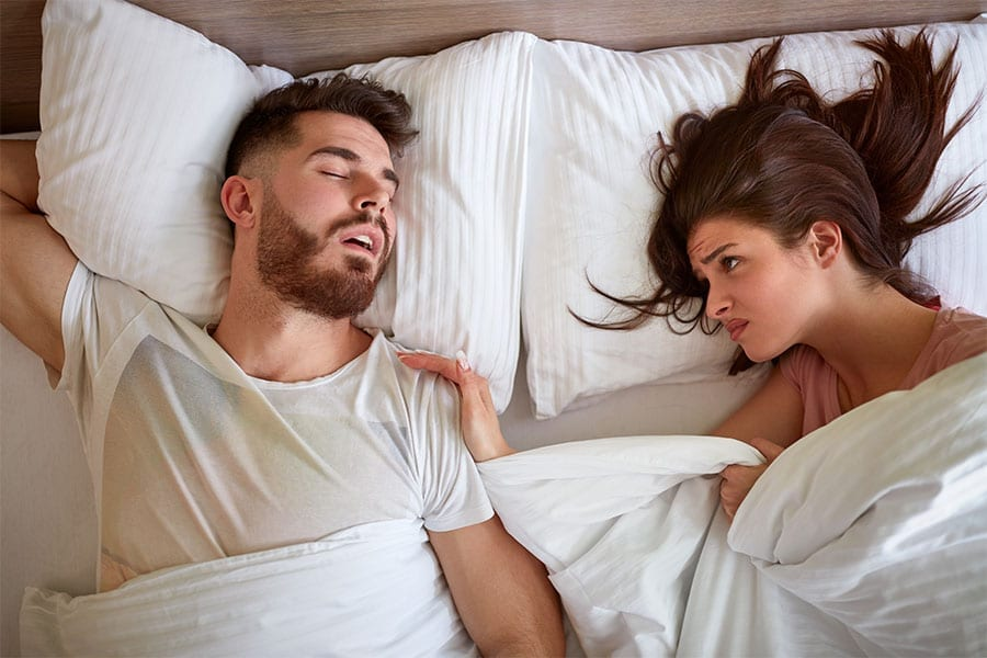 A woman lying in bed frustratingly looking at her sleeping husband.