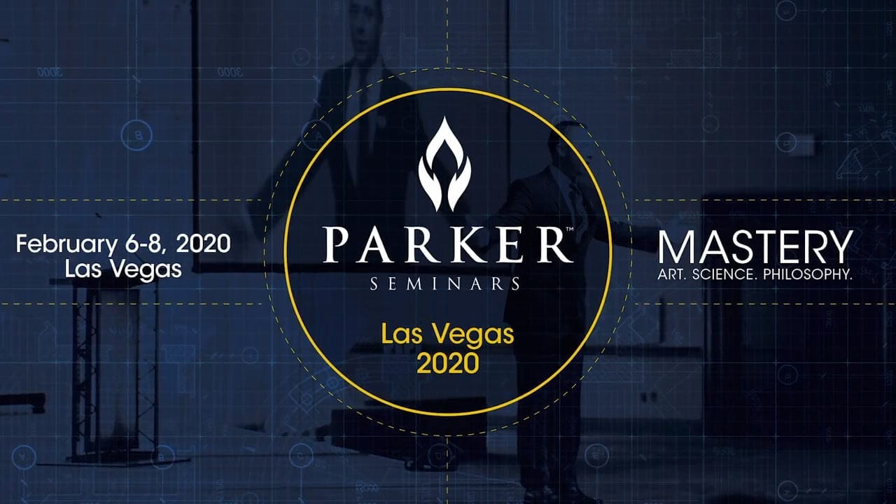 The Parker Seminars logo in front of someone speaking during a seminar with a transparent blue overlay.