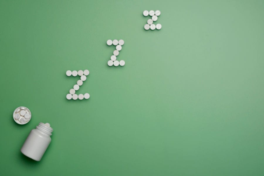 "A white pill bottle next to round, white pills that spell out ""Z Z Z""."