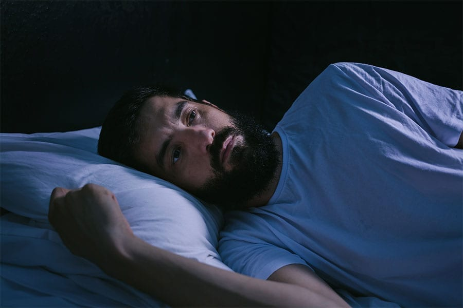 A bearded man lays awake in his bed.