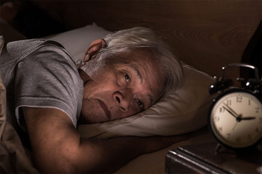 A senior man lies in bed staring at the alarm clock on his nightstand